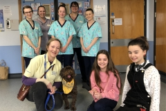 Kids presenters at Neptune Ward with staff and Rolo the Pets As Therapy dog